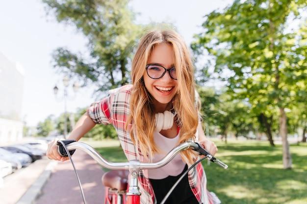 Zrelaksowana długowłosa dziewczyna w słuchawkach, jazda na rowerze. wspaniała pani z uroczym uśmiechem siedzi na rowerze.