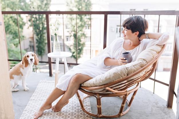 Zrelaksowana dziewczyna boso w białej sukni siedzi na krześle na balkonie i trzyma filiżankę herbaty