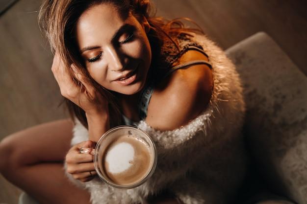 Zrelaksowana dziewczyna pije kawę w domu. wewnętrzny spokój. dziewczyna siedzi wygodnie na kanapie i pije kawę.