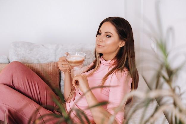 Zrelaksowana dziewczyna rano w piżamie w domu pije kawę wewnętrzny spokój dziewczyna siedzi wygodnie na sofie i popija kawę marząc o czymś.