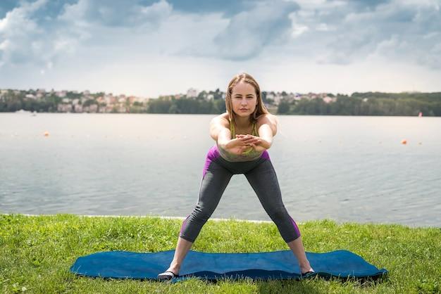 Zrelaksowana dziewczyna w odzieży sportowej robi rozciąganie, ćwiczenia medytacyjne, ćwiczenia oddechowe na macie do jogi w pobliżu jeziora