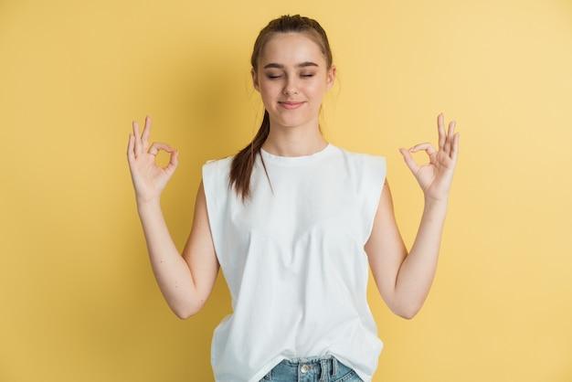 Zrelaksowana dziewczyna w swetrze pozowanie na białym tle na żółtym pomarańczowym tle. koncepcja stylu życia ludzi.