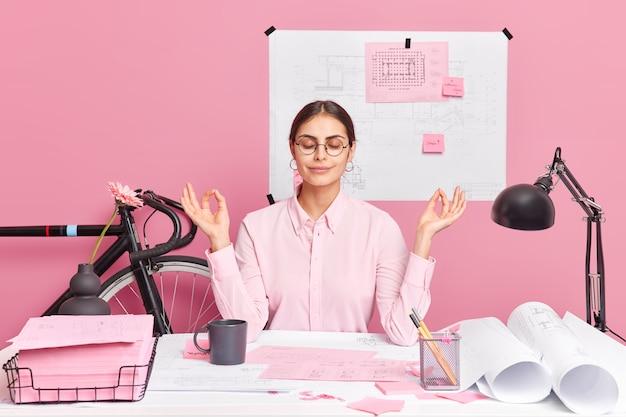 Zrelaksowana europejka, pracownica siedzi przy biurku, pracuje w domowym biurze, wykonuje gest medytacji, pokazuje znak mudry, zamyka oczy, rysuje szkice i plany