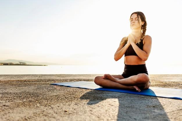 Zrelaksowana hiszpańska młoda kobieta z zamkniętymi oczami medytuje i ćwiczy jogę rano nad morzem - koncepcja stylu życia uważności, odnowy biologicznej i opieki zdrowotnej