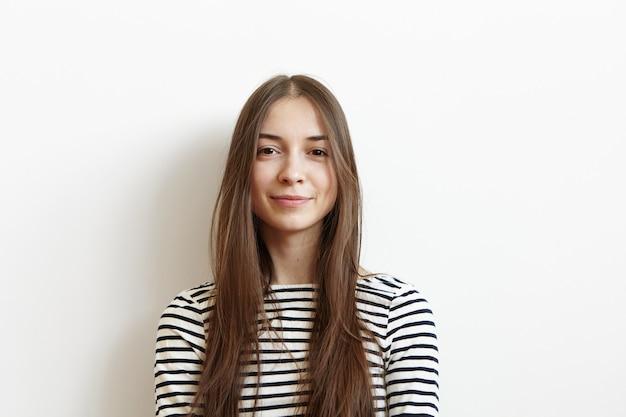 Zrelaksowana i beztroska młoda kobieta rasy kaukaskiej, ubrana w rozpuszczone długie włosy, uśmiechnięta radośnie