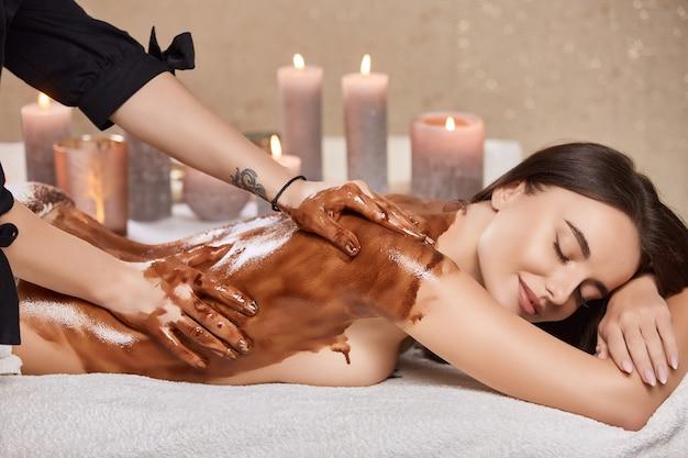 Zrelaksowana i piękna kobieta leżąca przy świecach i wykonująca zabiegi kosmetyczne z czekoladą na ciele