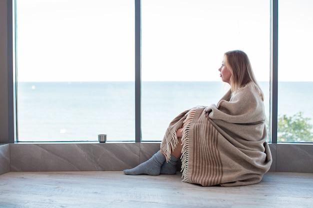 Zrelaksowana kaukaska kobieta siedzi na ciepłej podłodze w skarpetkach owiniętych wełnianym kocem w pobliżu dużego okna w świetle. jesienny nastrój, ciepło i komfort.