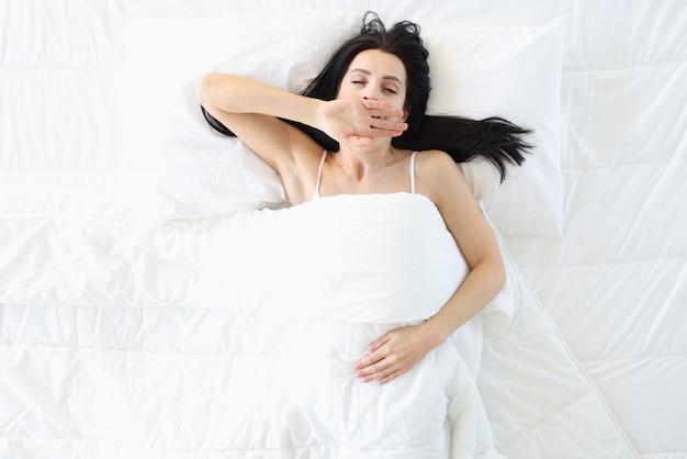 Zrelaksowana kobieta leży na dużym białym łóżku i ziewa, jak pozbyć się bezsenności