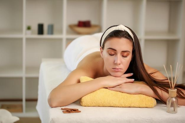 Zrelaksowana kobieta leży w salonie spa z zamkniętymi oczami, czeka na masaż