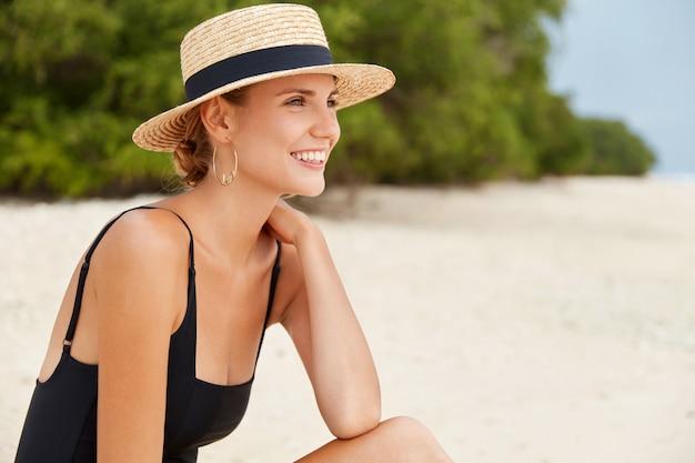 Zrelaksowana kobieta o atrakcyjnym wyglądzie ma radosny wyraz, opaloną skórę, nosi słomkowy kapelusz i kostium kąpielowy, spogląda na morze lub ocean, spędza wolny czas na plaży. koncepcja ludzi i rekreacji