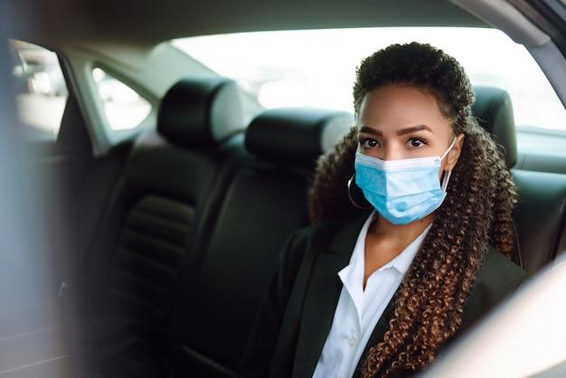 Zrelaksowana kobieta pasażera w ochronnej masce medycznej w taksówce.