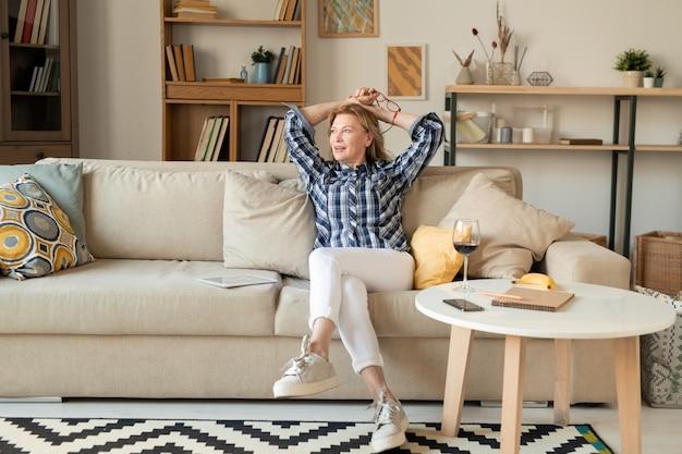Zrelaksowana kobieta w średnim wieku, ubrana na co dzień, siedząca na wygodnej kanapie w salonie i zastanawiająca się, co robić i dokąd się udać