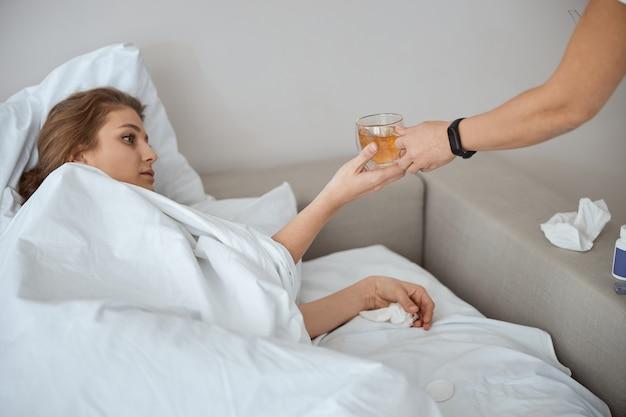 Zrelaksowana kobieta wyciągająca rękę podczas picia herbaty w łóżku