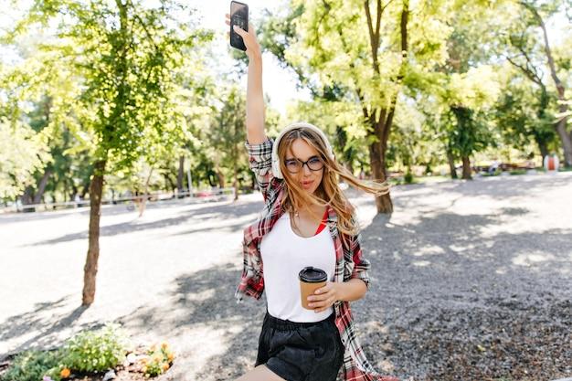 Zrelaksowana kobieta z filiżanką kawy zabawny taniec w parku. debonair blondynka w okularach, ciesząc się muzyką na naturze w godzinach porannych.
