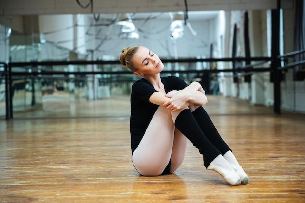 Zrelaksowana kobieta z zamkniętymi oczami odpoczywająca na zajęciach baletowych