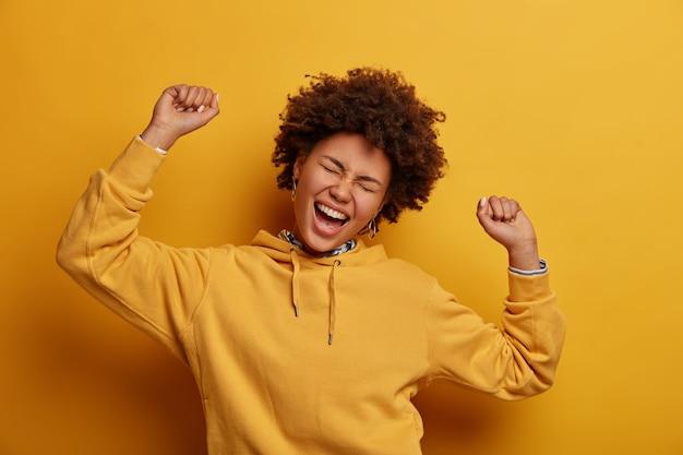 Zrelaksowana, leniwa, optymistyczna kobieta trzyma ręce uniesione do góry