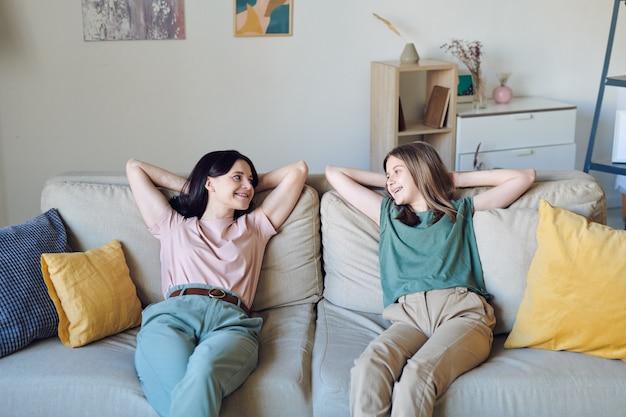 Zrelaksowana matka i nastoletnia córka siedzą na kanapie i wspólnie relaksują się w domu