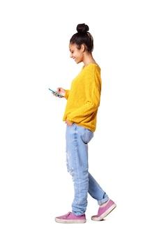 Zrelaksowana młoda afrykańska kobieta używa telefon komórkowego
