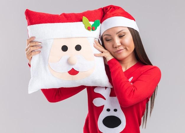 Zrelaksowana młoda azjatycka dziewczyna w świątecznym kapeluszu ze swetrem trzymająca świąteczną poduszkę na białym tle