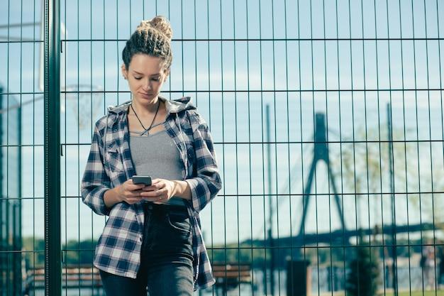 Zrelaksowana młoda dama ubrana w zwykłe ubrania i lekko uśmiechnięta, patrząc na ekran swojego nowoczesnego smartfona
