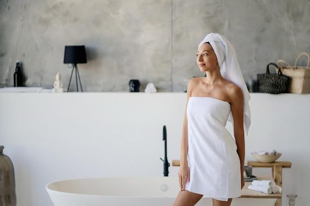 Zrelaksowana młoda kaukaska modelka w białym ręczniku