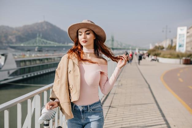 Zrelaksowana młoda kobieta bawi się rudymi włosami w górach