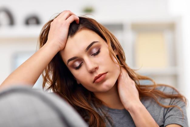 Zrelaksowana młoda kobieta ciesząca się odpoczynkiem na wygodnej kanapie