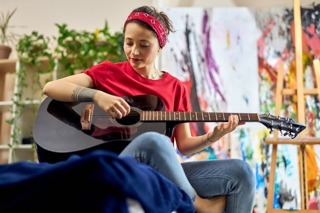 Zrelaksowana młoda kobieta grająca na gitarze, ucząca się grać, siedząc na łóżku w zwykłych ubraniach w
