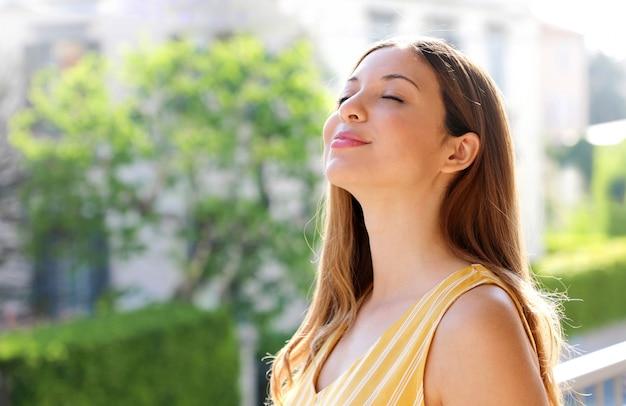 Zrelaksowana młoda kobieta oddychająca świeżym powietrzem na balkonie rano