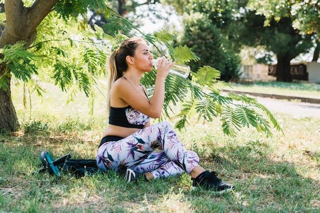 Zrelaksowana młoda kobieta pije wodę od butelki w ogródzie