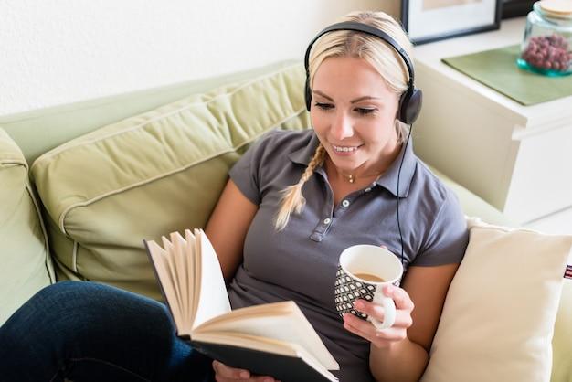 Zrelaksowana młoda kobieta siedzi na kanapie z filiżanką kawy w dłoni, czytając książkę i słuchając muzyki w domu
