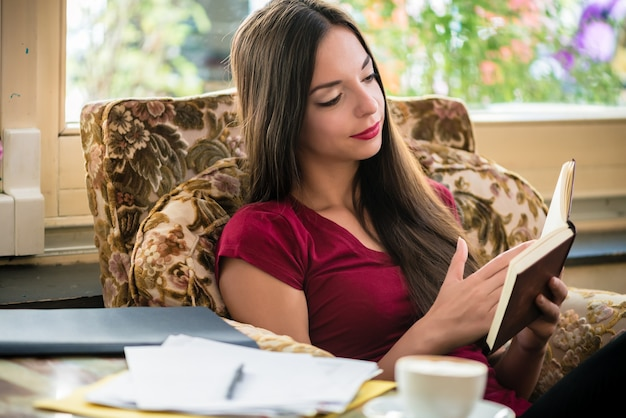 Zrelaksowana młoda kobieta siedzi podczas czytania ciekawej książki w domu