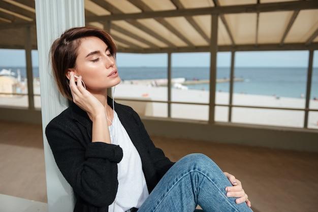 Zrelaksowana młoda kobieta siedzi z zamkniętymi oczami i słucha muzyki w altanie nad brzegiem morza