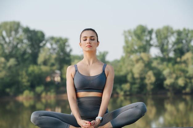 Zrelaksowana młoda kobieta uprawia jogę na świeżym powietrzu w pięknym miejscu nad rzeką
