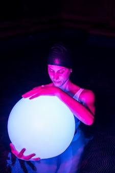 Zrelaksowana młoda kobieta w basenie z neonowym światłem