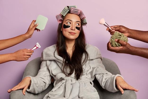 Zrelaksowana młoda kobieta w miękkim szlafroku, nosi kosmetyczne plastry pod oczami