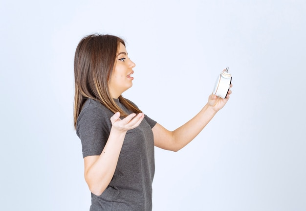 Zrelaksowana Młoda Kobieta W Piżamie, Zaskakująco Patrząca Na Budzik Darmowe Zdjęcia