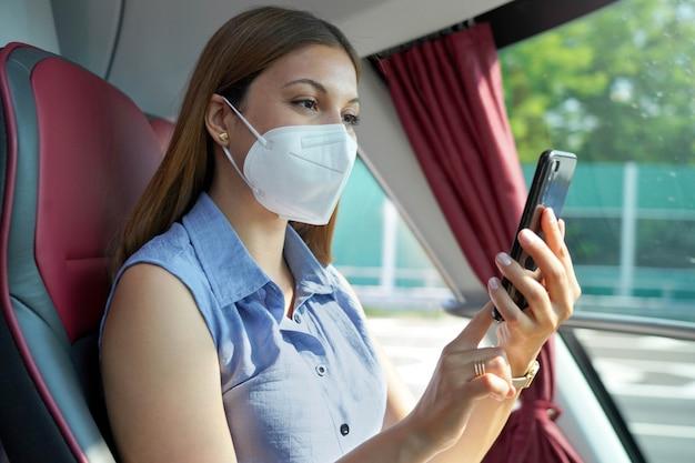 Zrelaksowana młoda kobieta z maską kn95 ffp2 korzystająca ze smartfona w transporcie publicznym