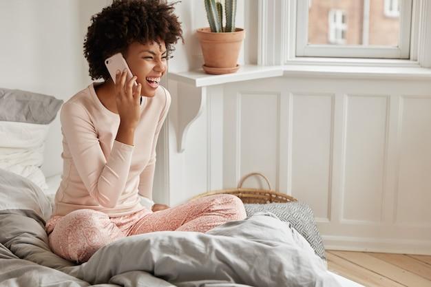 Zrelaksowana młoda kobieta z telefonem pozuje w domu
