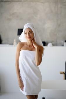 Zrelaksowana młoda modelka rasy kaukaskiej w białym ręczniku, czuje się wypoczęta po wzięciu prysznica, ma zdrową, czystą i miękką skórę, pozuje w przytulnej łazience. koncepcja kobiety, piękna i higieny.
