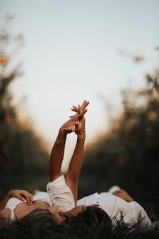 Zrelaksowana młoda para leży na zielonym trawniku, całuje się z zamkniętymi oczami i trzyma się za ręce.
