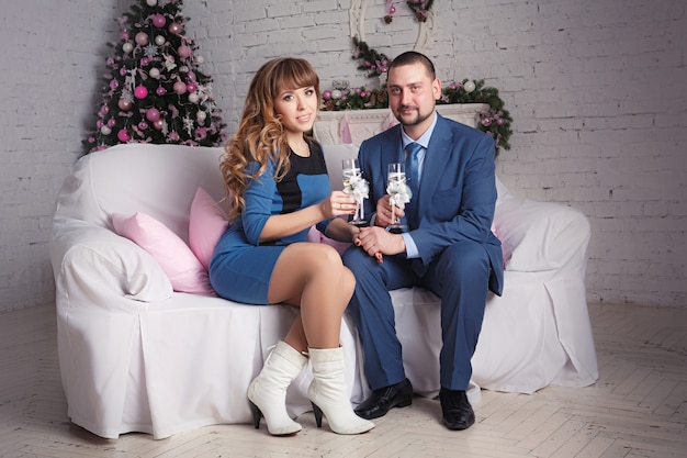 Zrelaksowana młoda para w domu w jasnym salonie z kieliszkami szampana