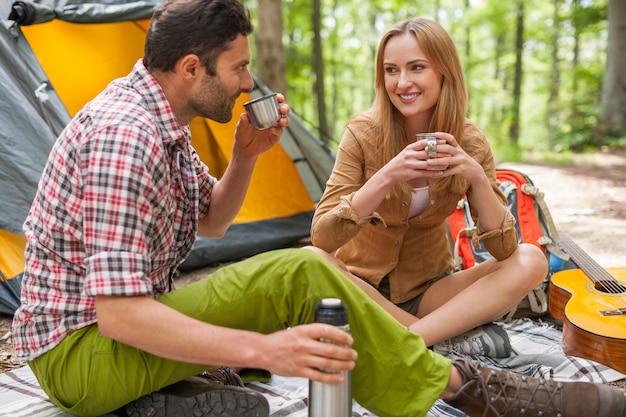 Zrelaksowana para w lesie i picie kawy