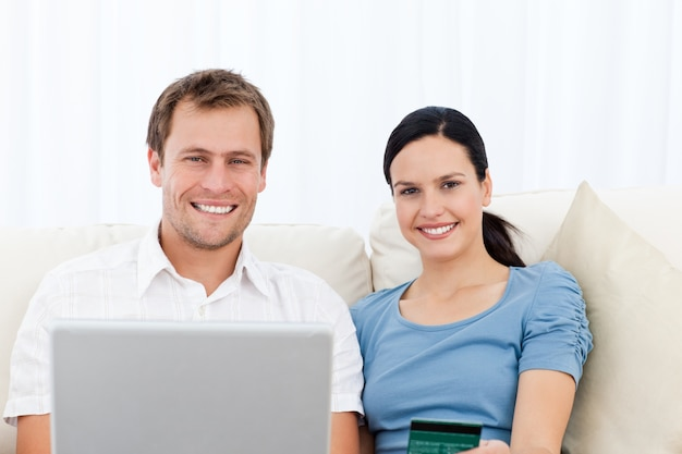 Zrelaksowana para z laptopem i kredytową kartą siedzi na kanapie