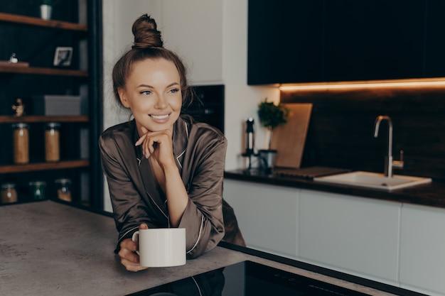 Zrelaksowana pozytywna młoda kobieta w jedwabnej przytulnej piżamie z filiżanką kawy w stylowym wnętrzu kuchni, ciesząc się wolnym czasem w domu, patrząc na bok z uśmiechem podczas rozpoczynania nowego pięknego dnia