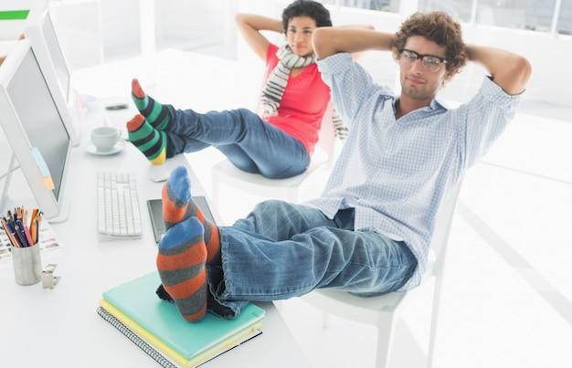 Zrelaksowana przypadkowa para z nogami na biurku w biurze