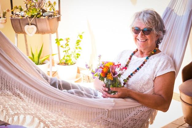Zrelaksowana starsza kobieta leżąc w białym hamaku, trzymając małe kwiaty.