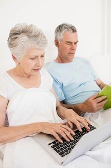 Zrelaksowana starsza para przy łóżkiem używa laptop i czytania boook