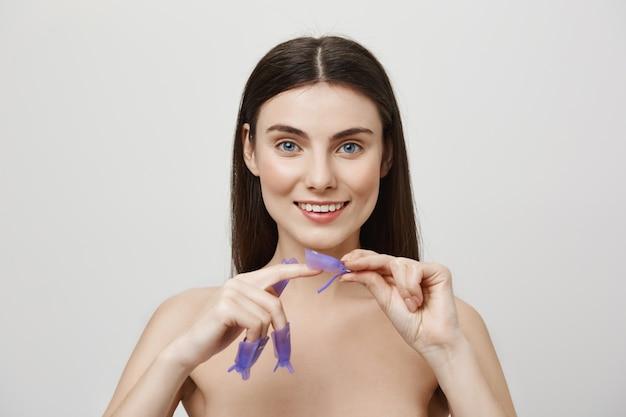 Zrelaksowana uśmiechnięta kobieta stojąca nago malowanie paznokci
