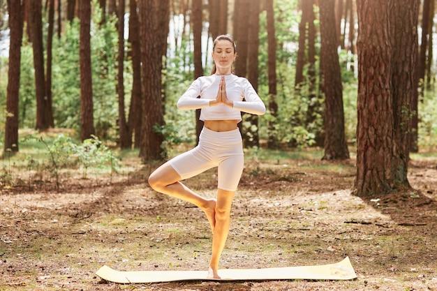 Zrelaksowana wysportowana kobieta stojąca na świeżym powietrzu z zamkniętymi oczami trzymająca dłonie razem, stojąca na jednej nodze, ubrana w sportową odzież, ciesząca się treningiem w pięknym lesie.